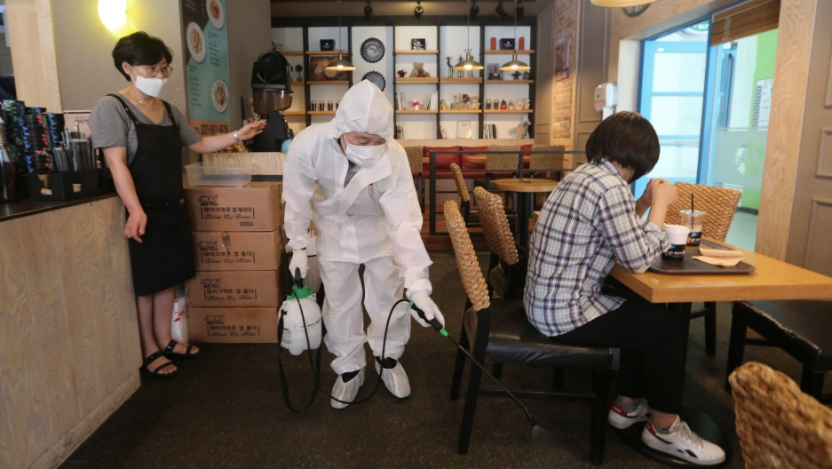 A worker dressed in white protective gear disinfects as a precaution against the coronavirus at a café in Goyang, South Korea, Aug. 25, 2020.