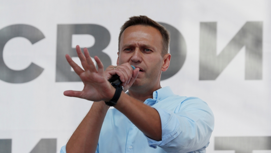 A man wearing a white shirt speaks on a microphone while gesturing with his hands.