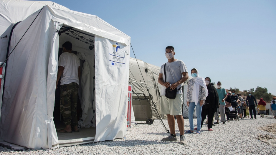 A white medical tent is shown with a long line of people waiting outside of it.