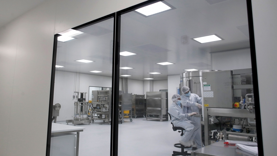 Two researchers are shown through large windows wearing full medical garments in a white laboratory.