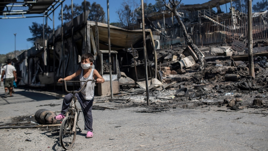 A young boy is shown sitting on a bike without tires in front of a destroyed structure at a refugee camp.