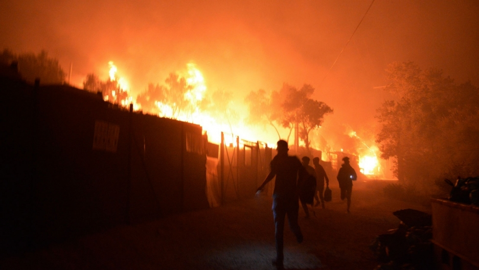 Several people are show running from a large fire engulfing several structures behind them.