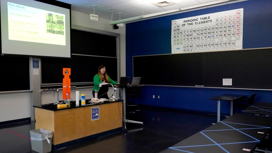 Sections of a table are seen blocked off with tape as assistant professor Jennifer Guerard speaks into laptops while teaching a foundations of chemistry remote class at the US Naval Academy, Aug. 24, 2020, in Annapolis, Md.