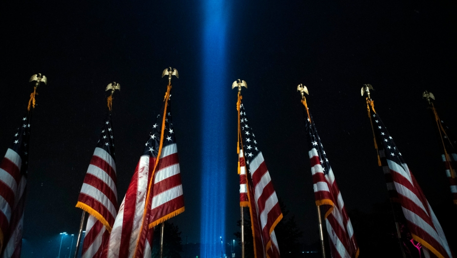 Beams of light are seen over American flags at the Pentagon, as part of a tribute marking the 19th anniversary of the 9/11 attack on the Pentagon, Sept. 9, 2020, in Washington, DC.