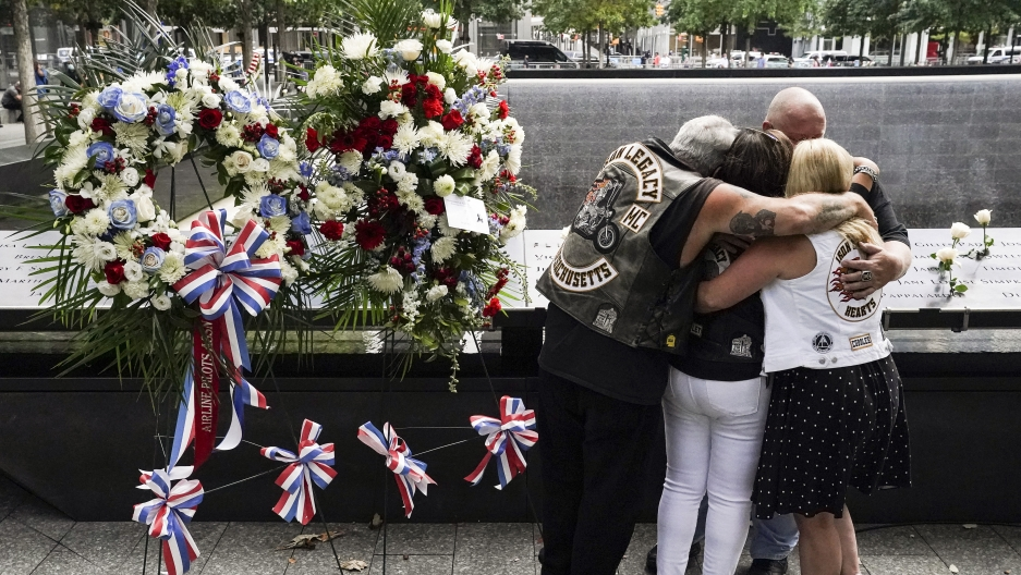 Mourners hug beside the names of the deceased Jesus Sanchez and Marianne MacFarlane at the National September 11 Memorial and Museum, Sept. 11, 2020, in New York.