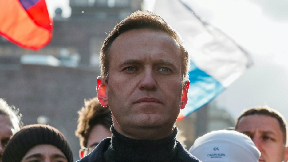Close up of Alexei Navalny, a white man with short hair wearing a turtle neck and a few people standing behind him