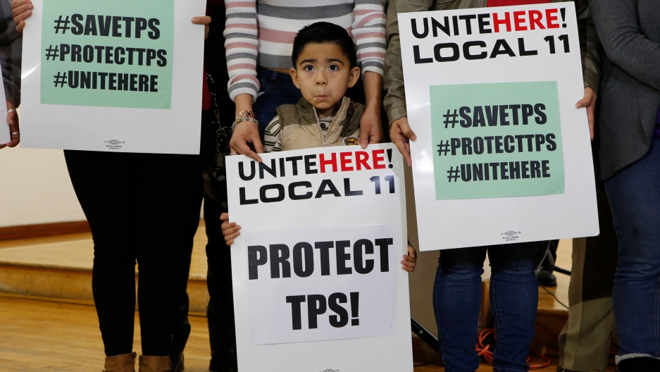"A young boy is shown holding a large white sign that says, ""Unite here! Local 11, Protect TPS!"" on it."