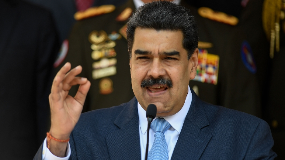 Venezuelan President Nicolás Maduro is shown speaking with his right hand rised.