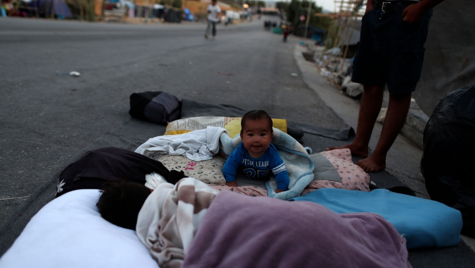 A small baby is shown looking at the camera and crawling on blankets out on a street.