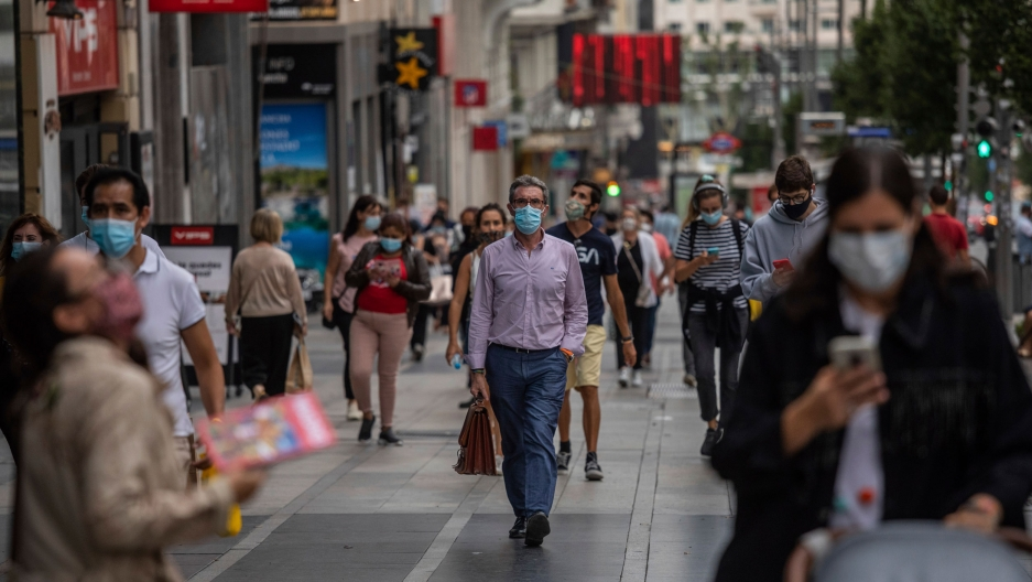 Dozens of people are show walking around a shopping district and wearing face masks in Madrid, Spain.