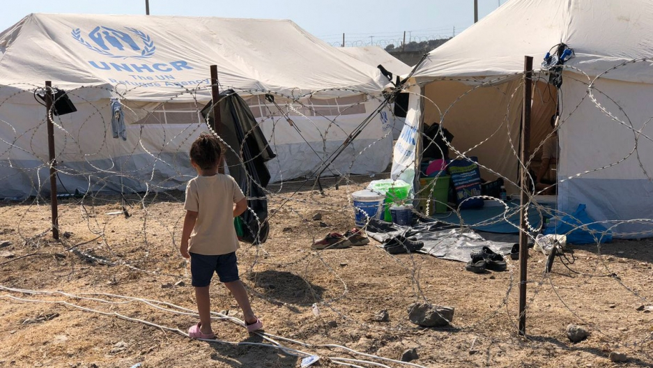 A young child is shown wearing shorts and a t-shirt walking past a barbed-wire fence and white UNHCR tents.