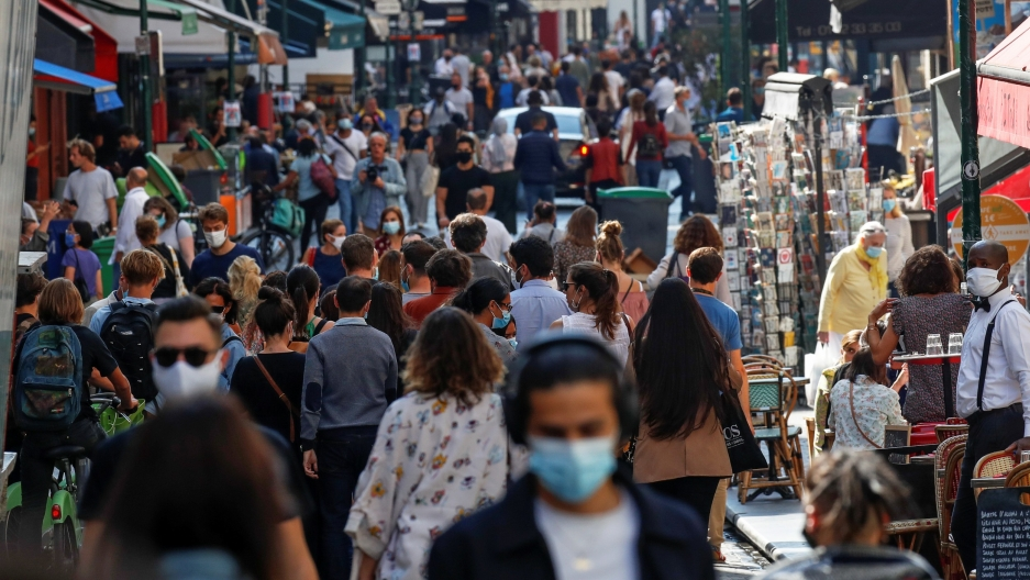 People wearing protective face masks walk in a busy street in Paris as France reinforces mask-wearing in public places as part of efforts to curb a resurgence of the coronavirus disease (COVID-19) across Europe, Sept. 18, 2020.
