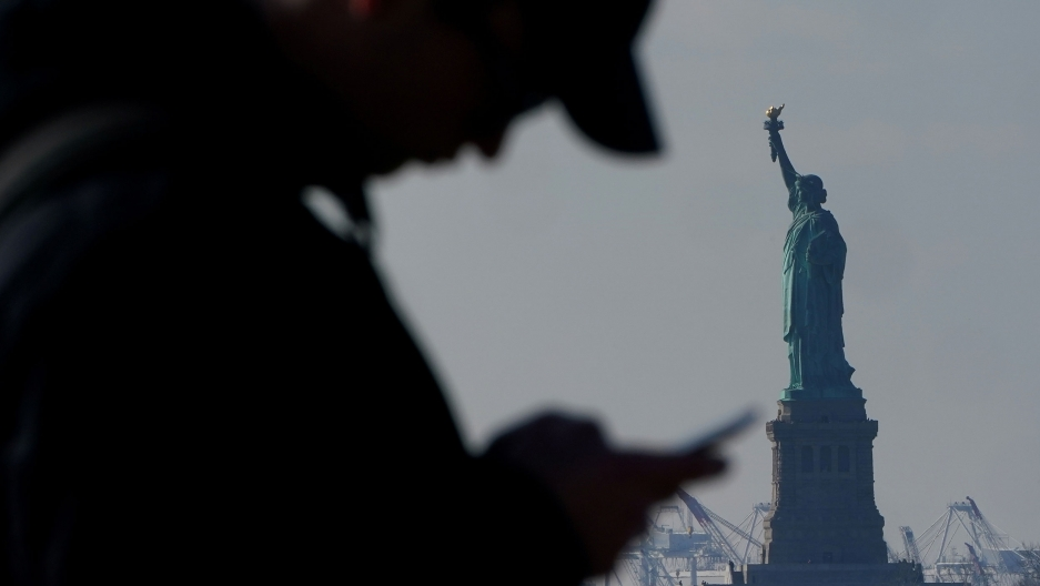 A man is shown in shadown hearing a hat and looking at a mobile phone with the Statue of Liberty in the background.
