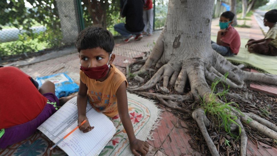 A young boy is shown wearing a red mask and holding a pencil while sitting on a mat next to a tree outside for school.