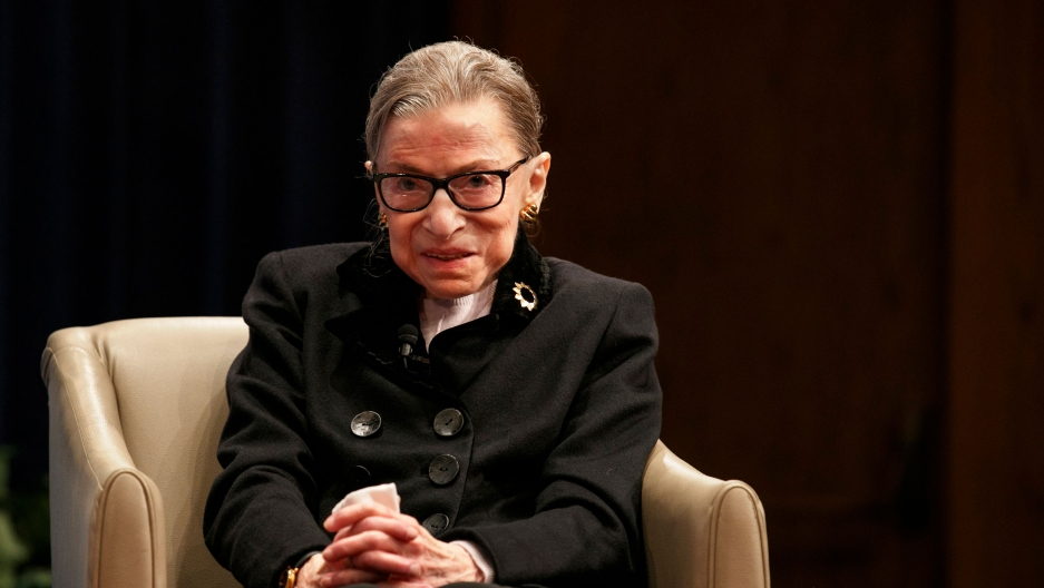 Supreme Court Justice Ruth Bader Ginsburg is shown sitting in a tan-color armchair and wearing a dark jacket with large buttons on the front.