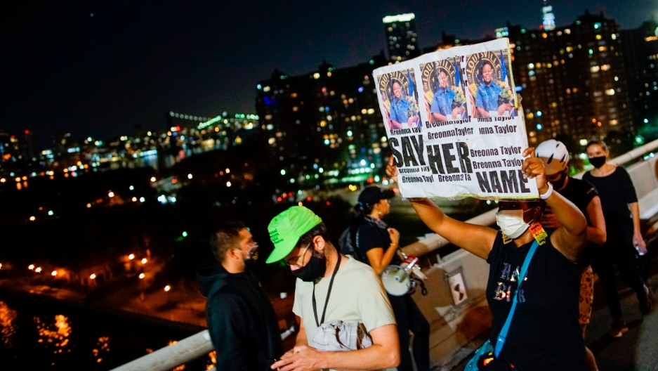 """A group of people are shown in a demonstration with one person carrying a sign that says, """"Say Her Name."""""""