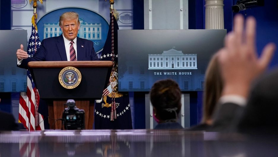 President Donald Trump is shown standing at a podium with TV monitoris and US flags behind him.