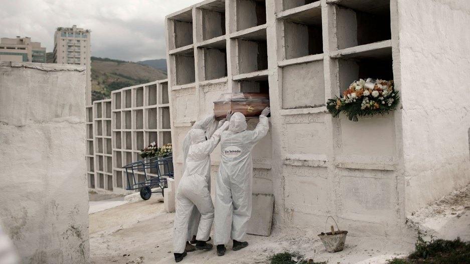 Three workers are shown wearing white protective clothing and placing a coffin into an empty slot in large white niche.