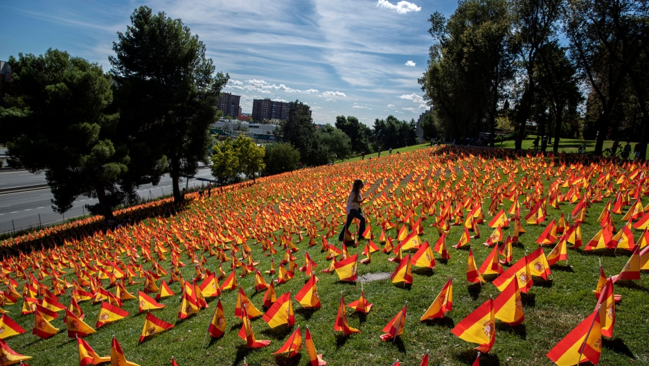 A woman walks among the Spanish flags placed in memory of coronavirus victims in Madrid, Spain, Sept. 27, 2020.