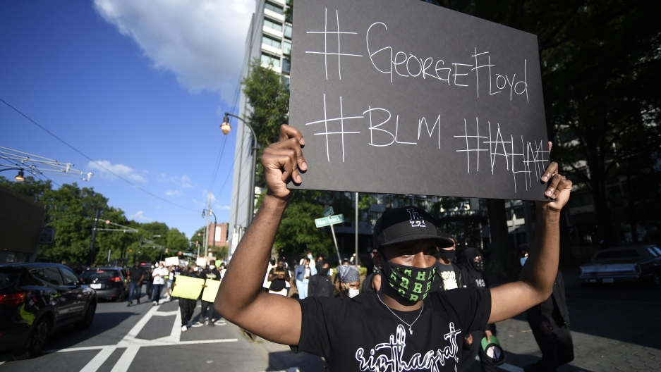 A demonstrator holding a sign reading #GeorgeFloyd and #BLM marches near Ebenezer Baptist Church in Atlanta, Georgia, May 30, 2020.