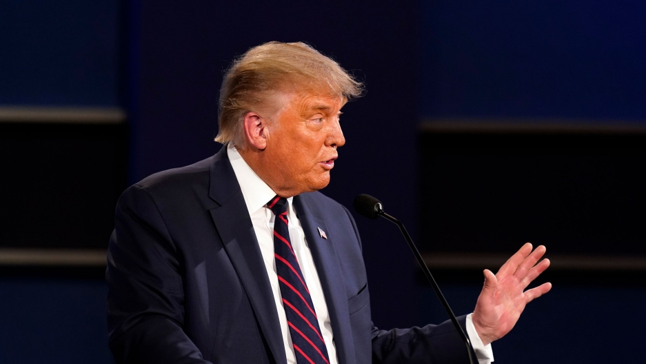 US President Donald Trump is shown standing behind a small microphone and wearing a dark suit with red and blue stripes while holding his left hand out.