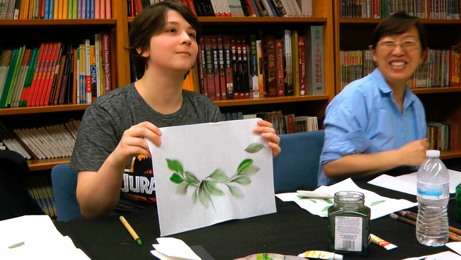 A white woman holds up a drawing of a plant next to a Chinese woman sitting at a table together