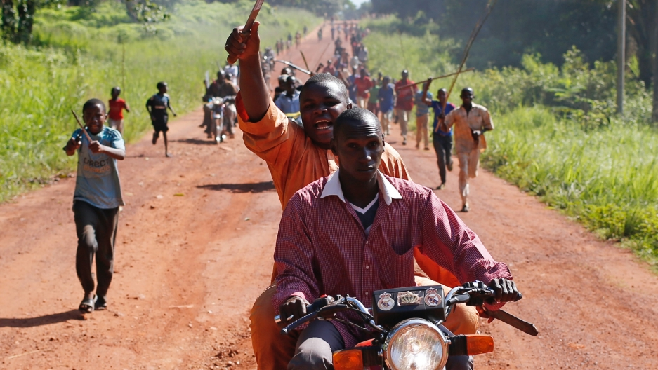 A man waves a machete in the air as he rides on the back of a motorcycle amid other protesters on foot on a long, dirt road.