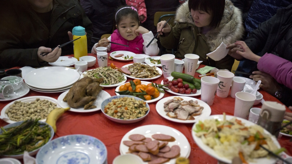 """A Chinese girl looks upon a table full of food during a """"1,000 people dumpling feast"""" in Liuminying village on the outskirt of Beijing, China,Jan. 27, 2017."""