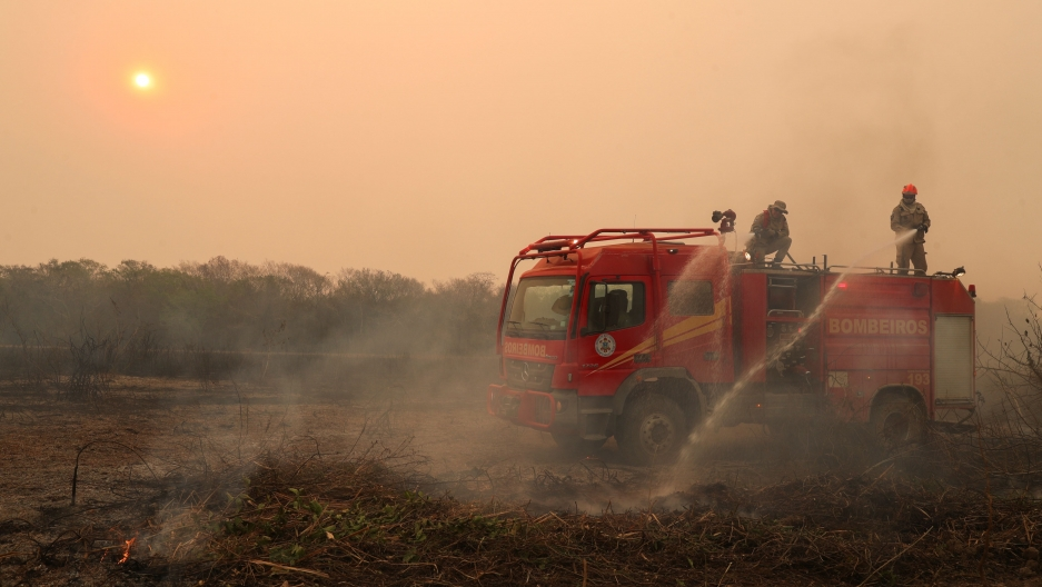 Firefighters work to extinguish a fire in a ranch amongst smoke in the Pantanal, the world's largest wetland, in Pocone, Mato Grosso state, Brazil, Aug. 28, 2020.