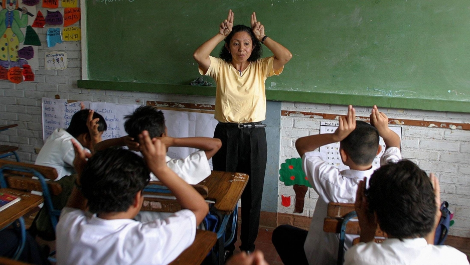 Teacher Ivania Guevara demonstrates during class to the children with hearing problems in the Melania Morales School in Managua, Nicaragua, Sept.22, 2004.