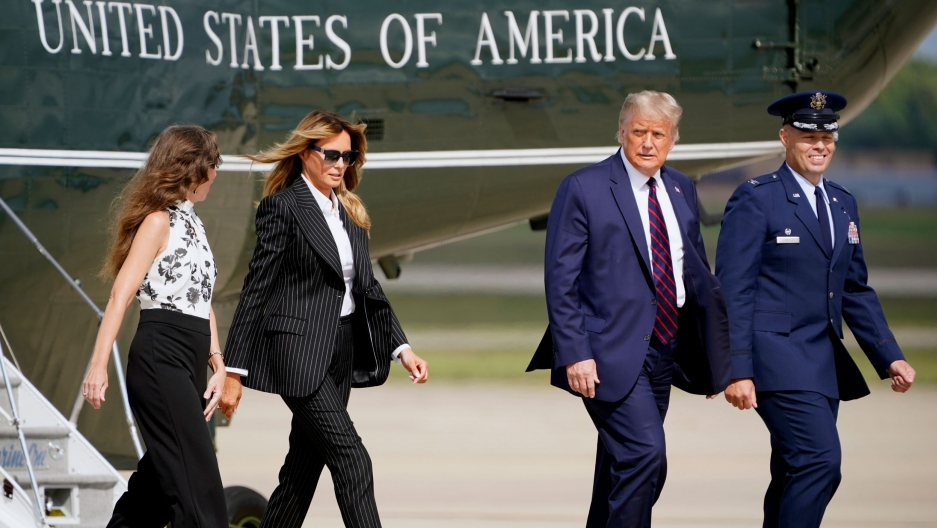 President Donald Trump and first lady Melania Trump walk are shown walking on a airport tarmac with the Marine One helicopter behind them.