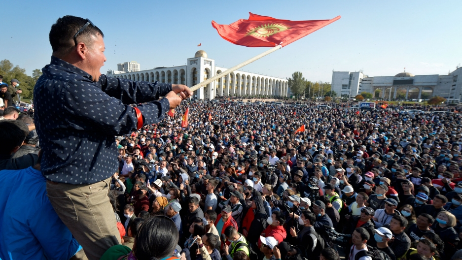 A man is shown waving the Kyrgyzstan flag as hundreds of people are crowded below in city square.