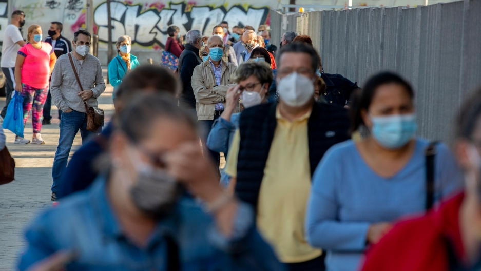 A long line of people are shown wearing face masks with wall painted with graffiti in the distance.