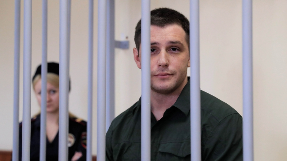 US ex-Marine Trevor Reed, who was detained in 2019 and accused of assaulting police officers, stands inside a defendants' cage during a court hearing in Moscow, Russia, March 11, 2020.