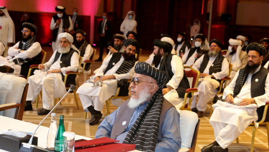 Several members of the Taliban negotiating delegation are shown seated in chairs spaced several feet from each other in a large room.