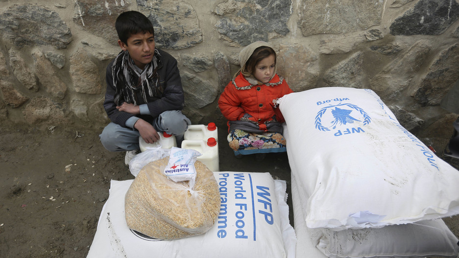 In this Jan. 24, 2017 file photo, children wait for transportation after receiving food donated by the World Food Program, in Kabul, Afghanistan.