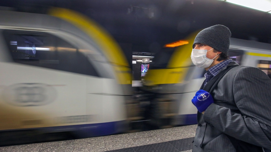 A man is shown wearing a face mask and winter hat as a train passed by in blurred motion.