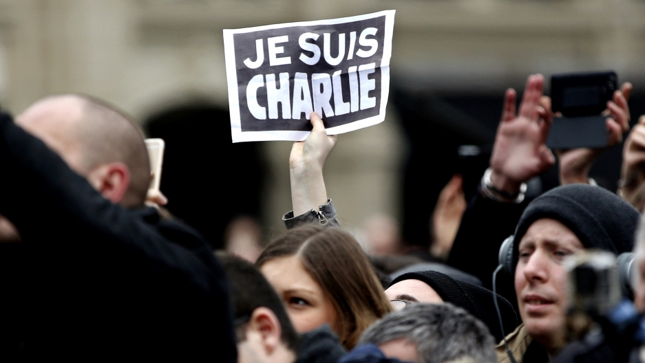 "A person holds up a ""Je Suis Charlie"" (""I am Charlie"") sign during a ceremony at Place de la Republique square to pay tribute to the victims of the 2015 shooting at the French satirical newspaper Charlie Hebdo, in Paris, France, Jan. 10, 2016."