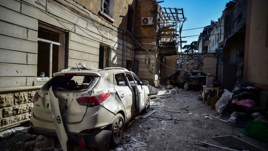 A heavily damaged car is shown in an alley in the nearground with several damaged buildings in the distance.