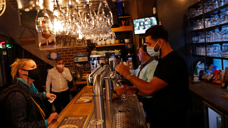 A bartender is shown pulling a draft beer while wearing a face maks with glasses hanging above the bar.