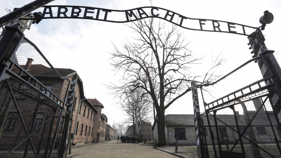 "The entrance gate at the Nazi concentration camp Auschwitz-Birkenau with an iron sign over the gate that reads ""work makes one free."""