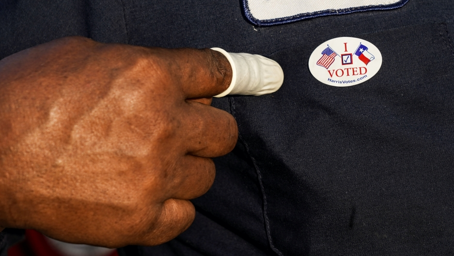 "A person wearing a finger sack points at an ""I Voted"" sticker after casting ballot for the upcoming presidential election as early voting begins in Houston, Texas, Oct. 13, 2020."