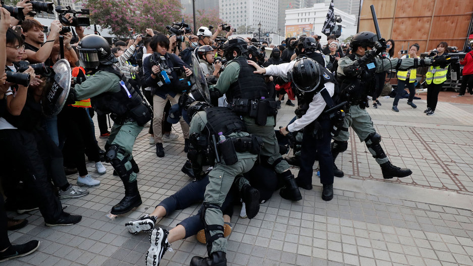 Riot police arrest protesters during a rally to show support for Uighurs and their fight for human rights. Thousands of demonstrators attended a rally to protest against China's policy on the Uighur minority, Hong Kong, Dec. 2019.