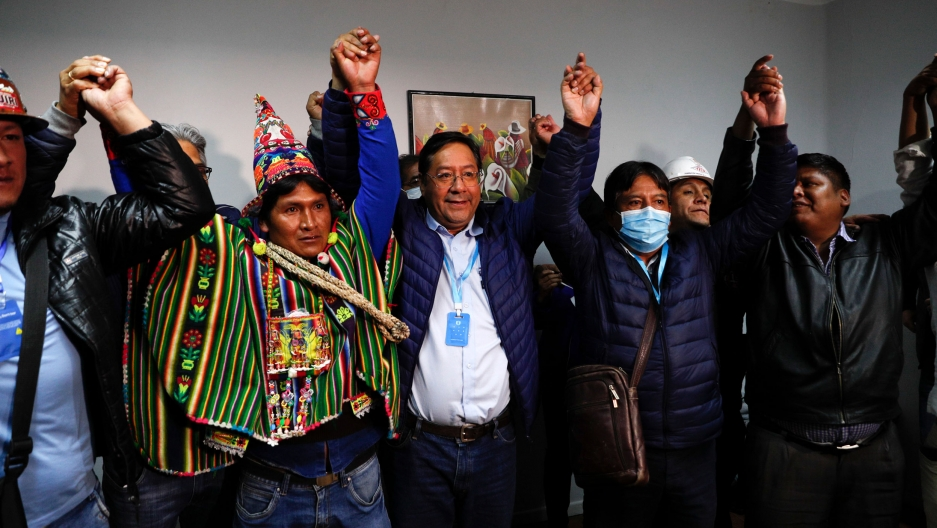 Several Bolivian politicians are shown in a room holding their hands in the air in celebration.