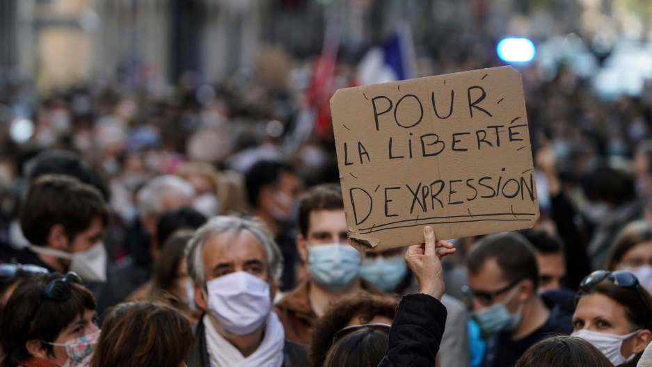 "A large crowd of demonstrators are with one person holding a sign that read, ""Pour La Liberte D'Espression,"" or ""For the freedom of speech"" in English."