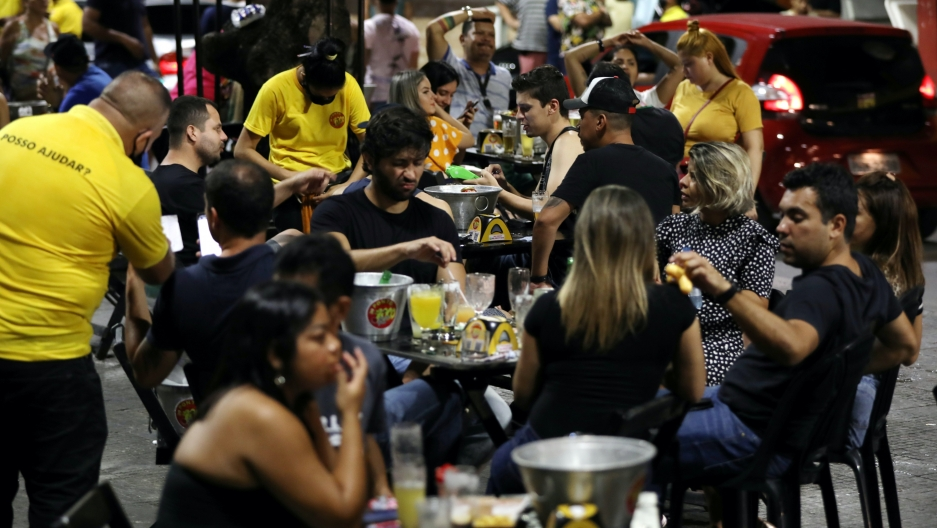 People enjoy beers and food at an outdoor restaurant where waitstaff wear yellow shirts.