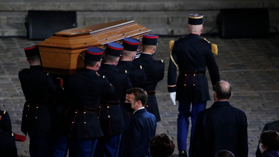 Eight uniformed officers are shown carrying a brown wooded coffin.