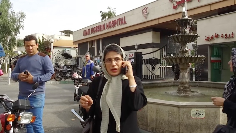 A woman wears a scarf while talking on a phone on a Tehran street