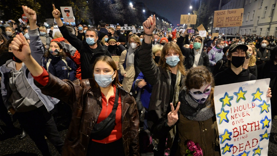 A large crowd of people are show in the street — many wearing protective face masks and carrying signs.