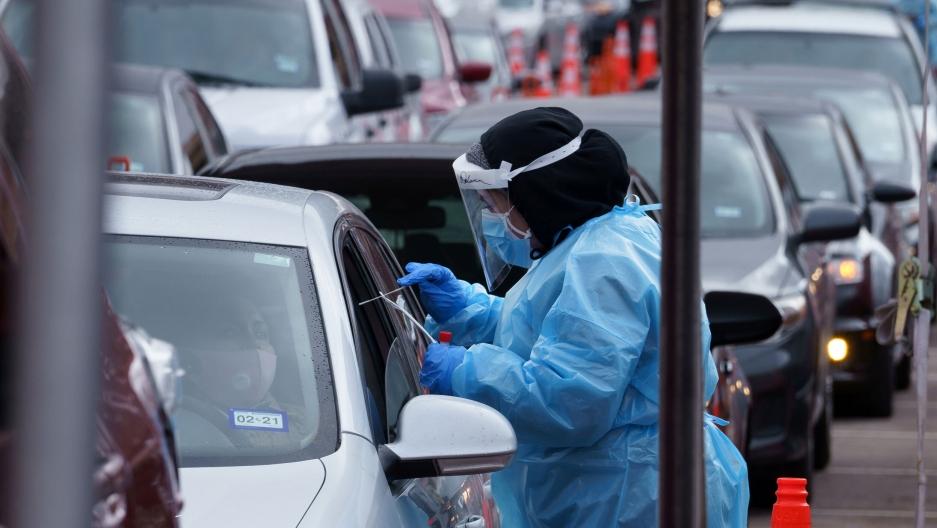 A nurse takes a swab sample at a drive-through coronavirus test site at the University of Texas El Paso in El Paso, Texas, Oct. 27, 2020.